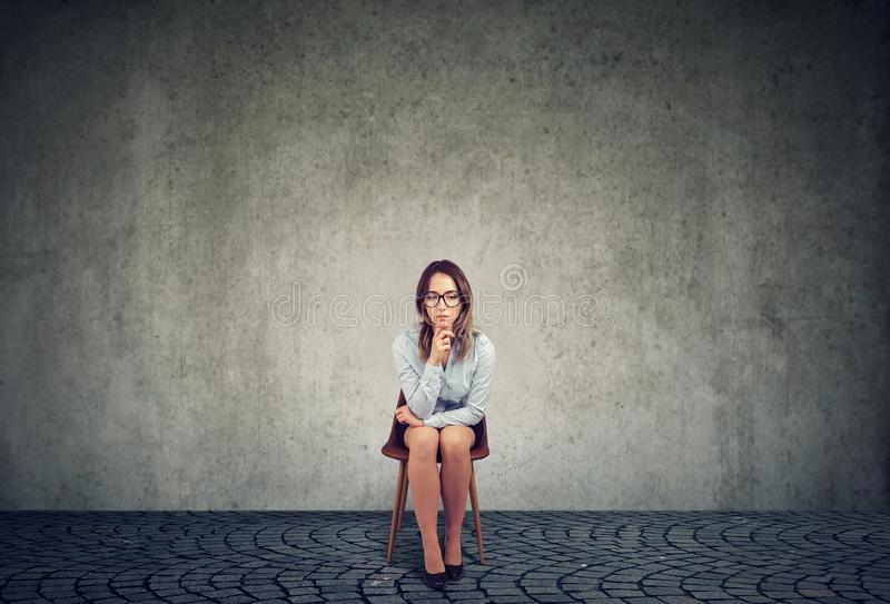 Pensive sad businesswoman sitting on a chair royalty free stock photography