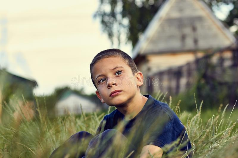 Pensive and sad look of a child with cerebral palsy. Summer evening boy sitting in the grass and looking into the royalty free stock images
