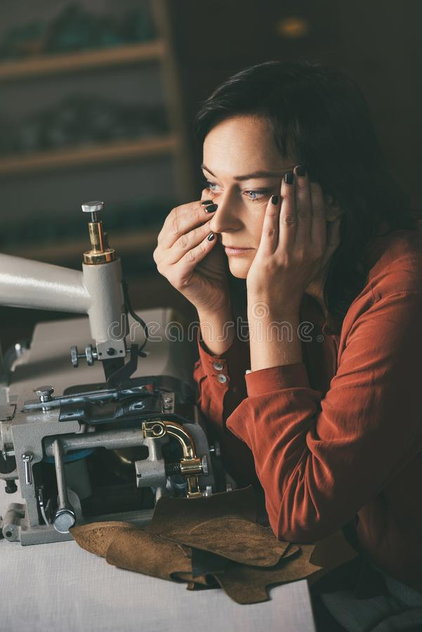 Pensive seamstress looking away while working with sewing machine and leather. At shoemaker workshop royalty free stock images