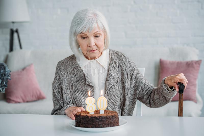 pensive senior lady sitting at table with birthday cake with candles alone stock images