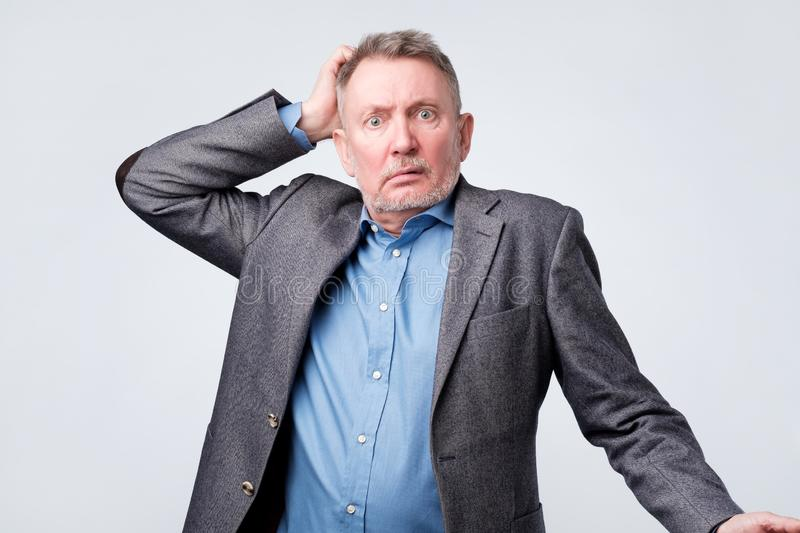 Pensive senior man in suit scratching his head royalty free stock image