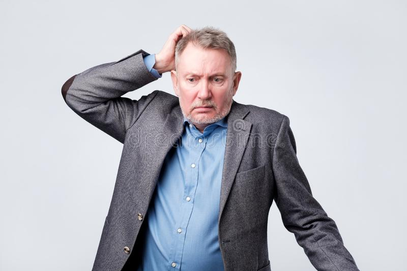 Pensive senior man in suit scratching his head stock images