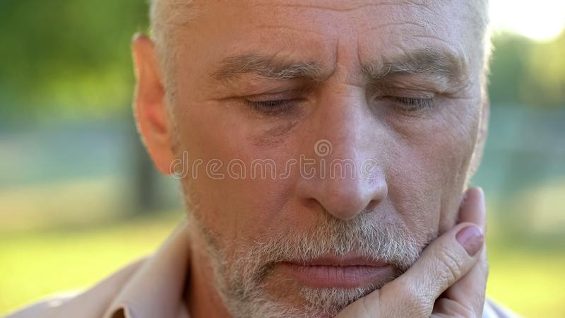 Pensive senior man thinking over life injustice, wife touching his face, support royalty free stock photos
