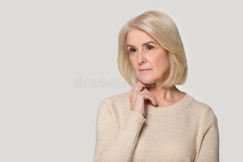Pensive senior woman isolated on grey background thinking royalty free stock photography