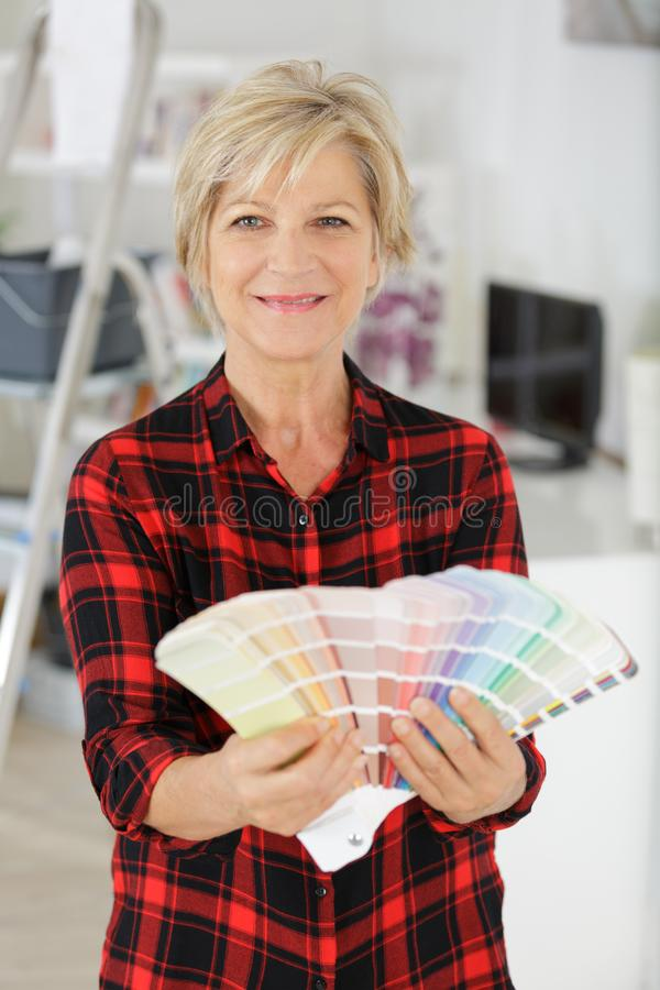 Pensive senior woman looking at color swatch stock images