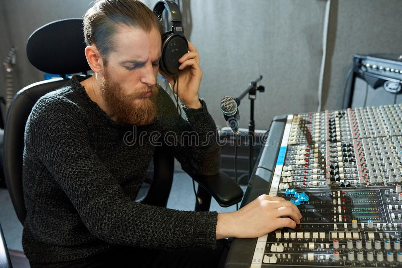 Concentrated music designer regulating sounds in studio stock photo