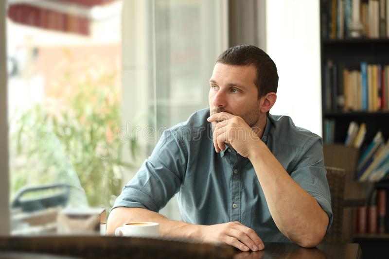 Pensive man in a coffee shop looking through a window. Pensive serious man in a coffee shop looking at side through a window stock photography