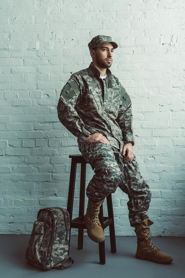 Pensive soldier in military uniform sitting on chair against white. Brick wall stock images