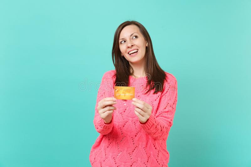 Pensive stunning young girl in knitted pink sweater looking up, holding in hands credit card isolated on blue turquoise royalty free stock photos