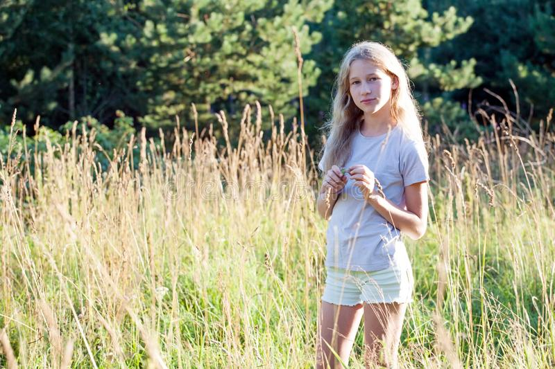 Teenager girl standing on summer meadow background. Pensive teenager girl standing on summer meadow outdoor background royalty free stock photo