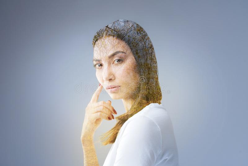 Pensive tender woman wondered about her thought. Compromising thought. Musing reflective serious woman standing on the grey background while touching her face royalty free stock image