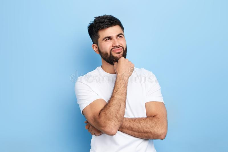 Pensive thoughtful handsome man making up a plan, idea stock image