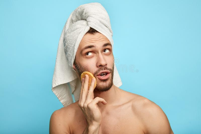Pensive thoughtful handsome man with moisturizer looking up royalty free stock image