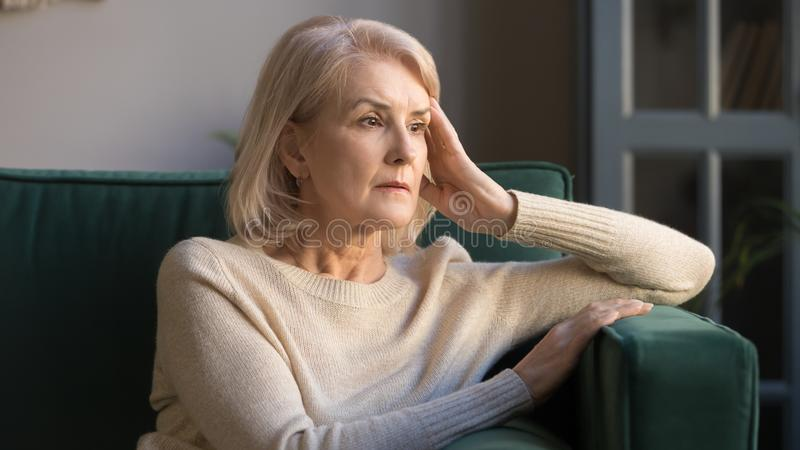 Pensive middle aged lady looking away sit alone at home royalty free stock photography