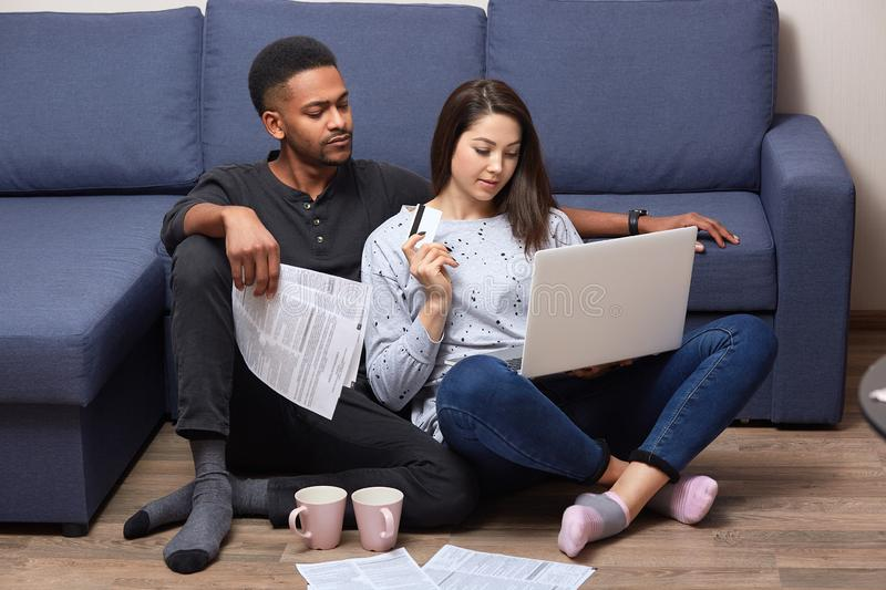 Pensive thoughtful woman sitting near her husband, raising her hand, holding credit card, looking attentively at screen, applying royalty free stock photo