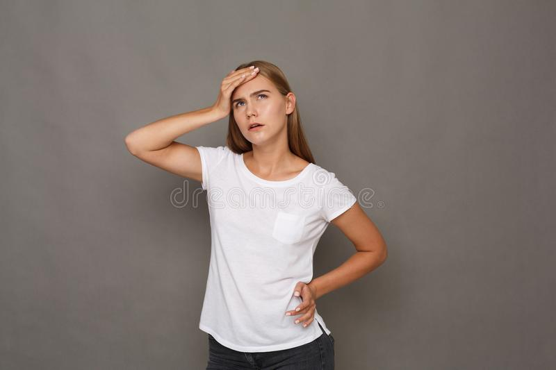 Concentrated woman thinking on gray background royalty free stock images