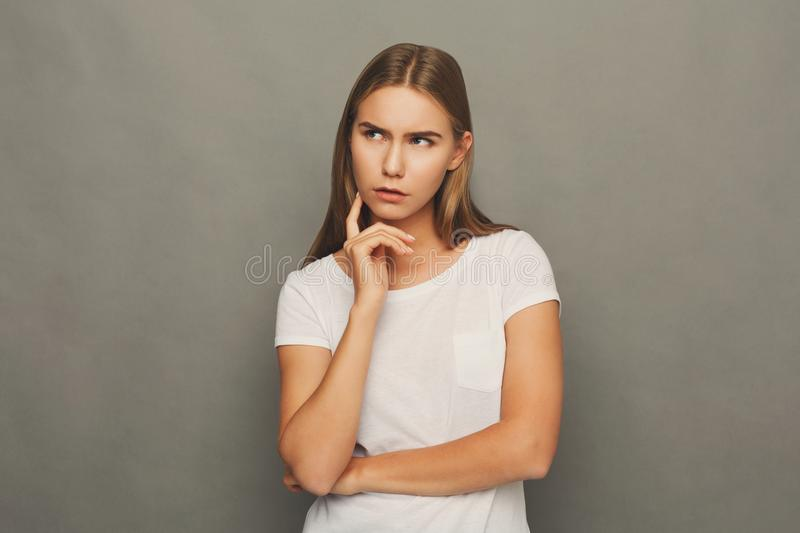 Concentrated woman thinking on gray background royalty free stock photography