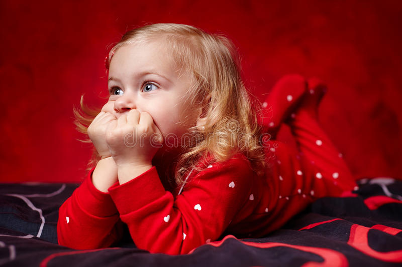 Pensive Toddler Girl Laying In Bed With Hands On Chin Stock Photography