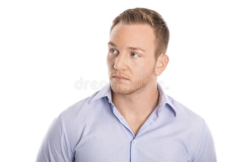 Pensive and unhappy isolated young blond businessman in blue shirt looking sideways. stock images