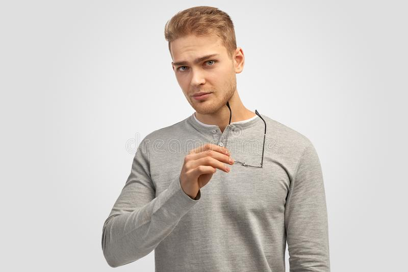 Pensive unshaven man holds glasses, looks thoughtfully directly into camera, thinks about something important. Dressed in stylish shirt, has fashionable stock images
