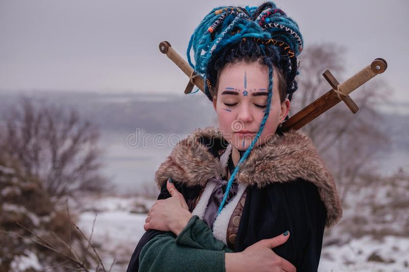 Pensive Viking woman with a sword in a black long mantle with fur. portrait of a dreamy girl with closed eyes. Female with blue royalty free stock images