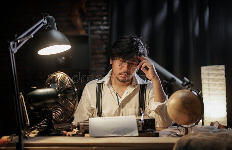 Pensive Vintage Man Finding Inspiration for Typewriting Work. 1950s Scene Setup royalty free stock image