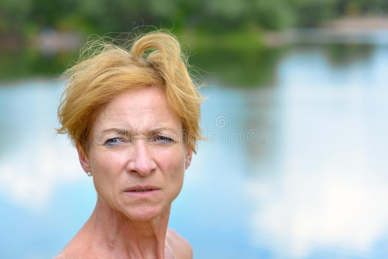Pensive watchful woman looking aside. With a serious expression in a close up head shot against tranquil lake stock images