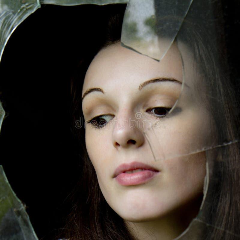 Pensive woman behind a broken window. royalty free stock photo