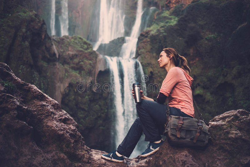 Pensive woman with coffee mug near Ouzoud waterfall in Morocco. stock image