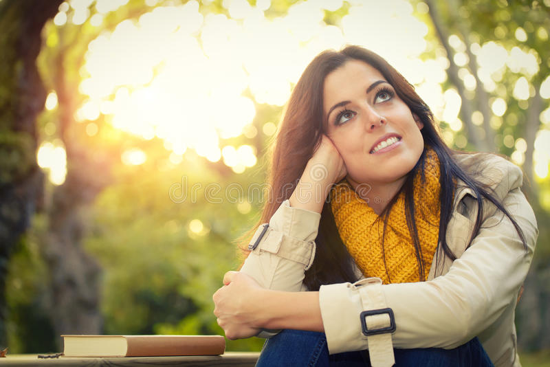 Pensive woman day dreaming in park royalty free stock images