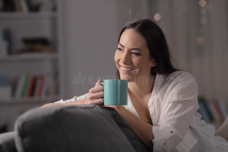 Pensive woman drinks coffee looking at side in the night at home stock images