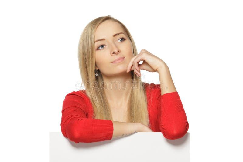 Pensive woman leaning on blank whiteboard