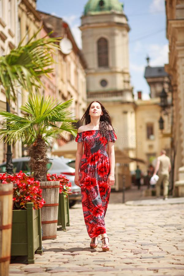 Pensive woman in long colorful dress on street of tourist old European city royalty free stock photos