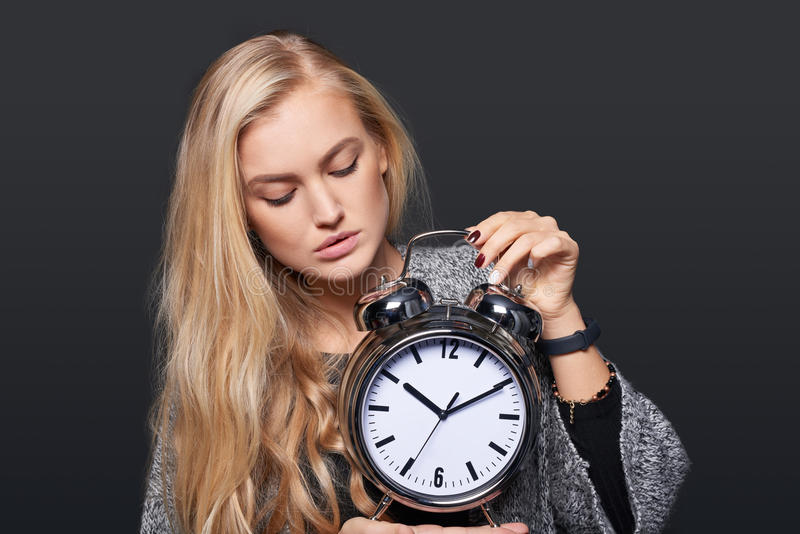 Pensive woman looking at alarm clock royalty free stock photos