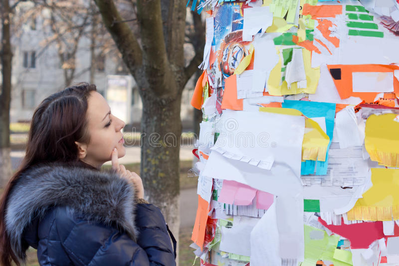 Pensive woman reading advertisements on a board royalty free stock photos