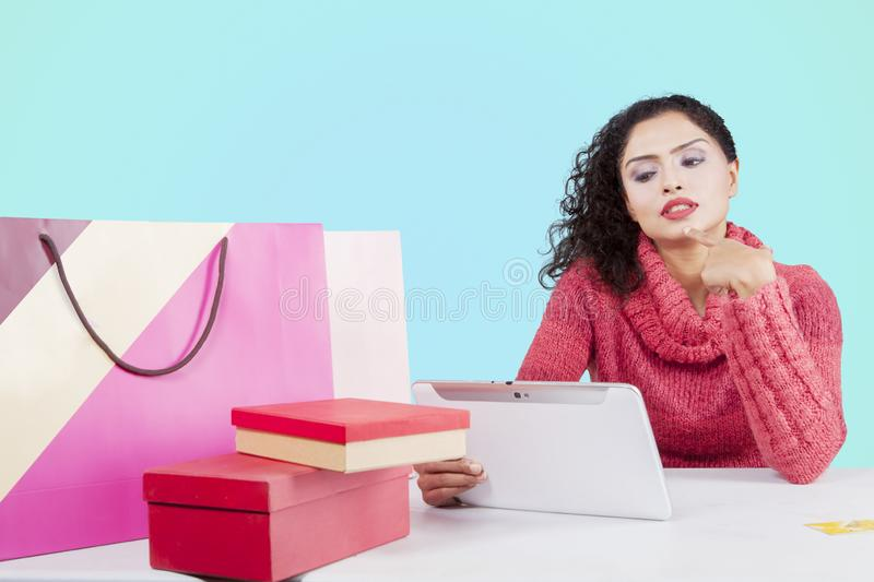 Pensive woman shopping online on studio. Image of pensive woman shopping online by using a digital tablet while sitting in the studio stock photo