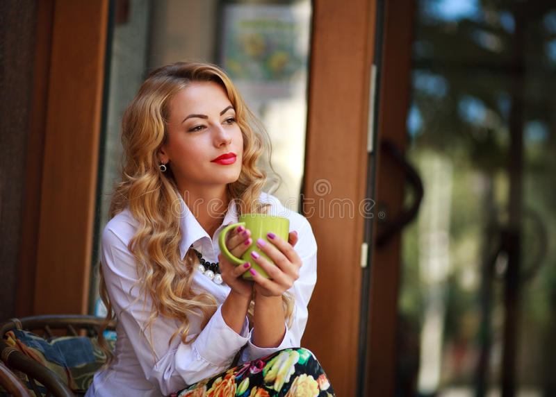 Pensive woman sitting with coffee cup and has a rest. In spring cafe outdoors and dreaming looking far away stock photography