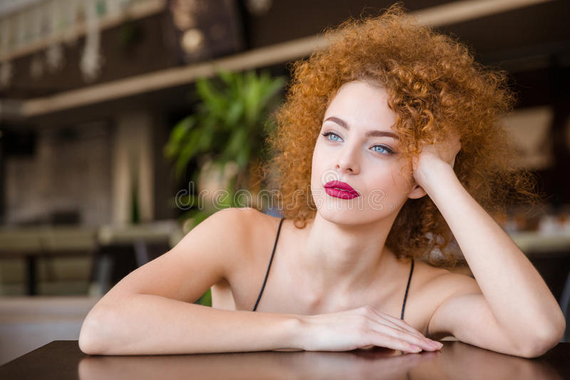 Pensive woman sitting at the table in restaurant royalty free stock photos