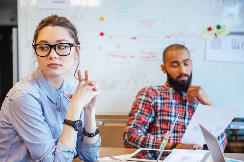 Pensive woman sitting and thinking while her male colleague reading royalty free stock photography