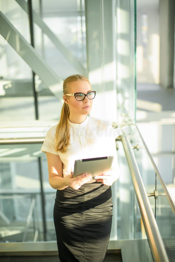 Pensive woman skilled financier in official wear and glasses holding in hands touch pad computer and looking away stock photo