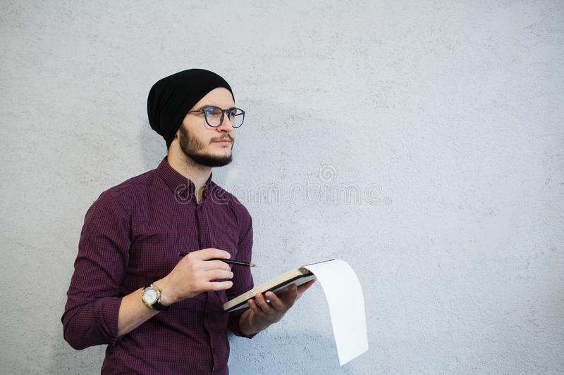 Pensive writer man holding a notebook and pencil. Bearded and dressed with shirt and black hat, wearing glasses. royalty free stock photos