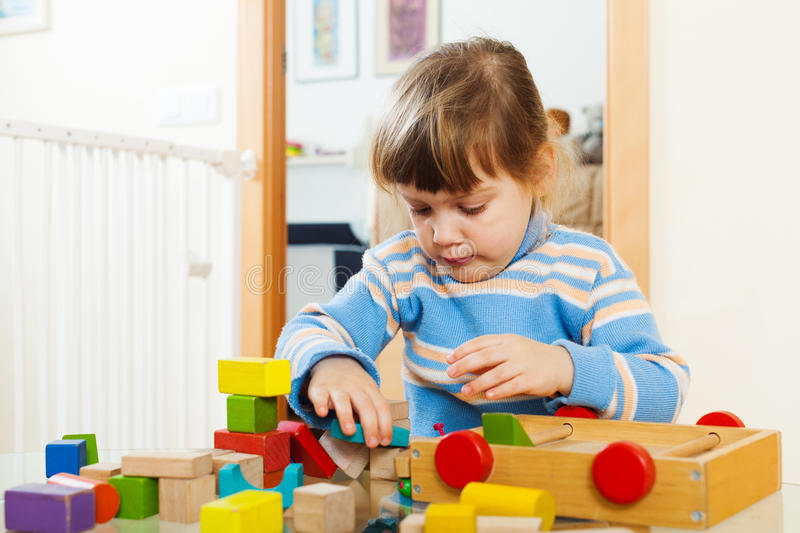 Pensive 3 years child playing with wooden toys. In home interior stock photo