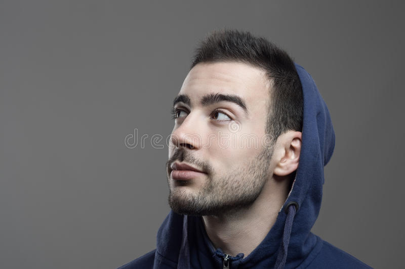 Pensive young bearded man looking up wearing blue hooded shirt royalty free stock image