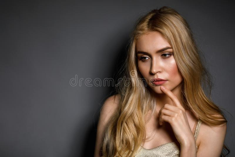 Pensive young beautiful girl on gray background with copy space royalty free stock photos