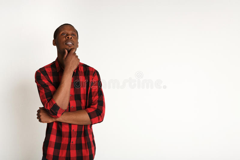 Pensive young black man portrait at studio background. stock photography