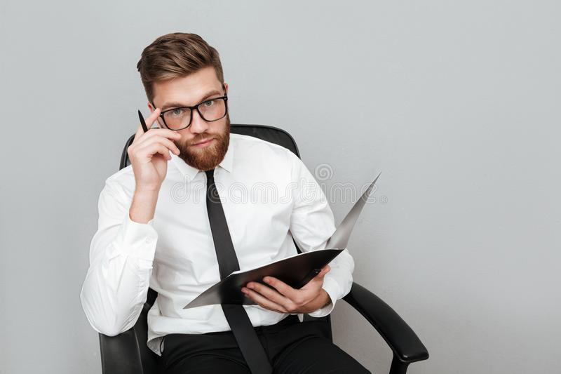 Pensive young businessman in eyeglasses holding a folder royalty free stock photo