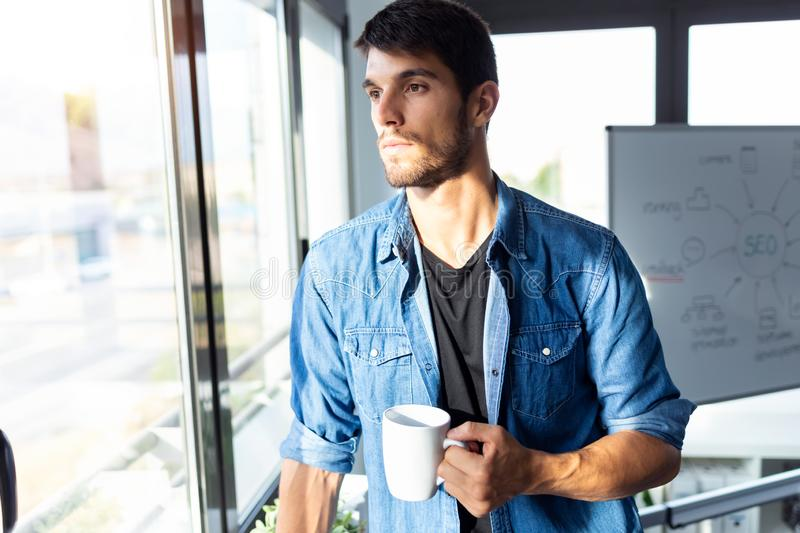 Pensive young businessman looking through the window while drinking coffee and taking a break in the office stock photos