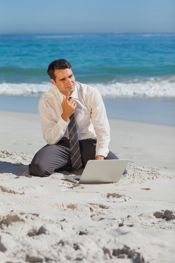 Pensive young businessman sitting on the sand with his laptop