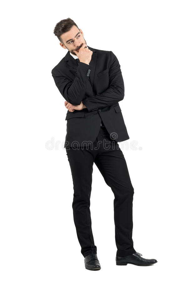 Pensive young businessman thinking with hand over his mouth looking away royalty free stock image