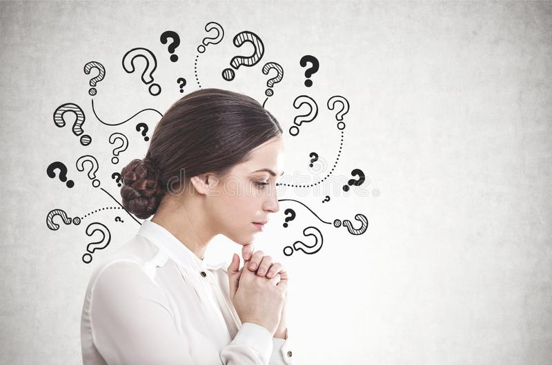 Pensive young businesswoman, many questions stock photography